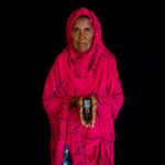 Older woman in red robe holding a mobile phone