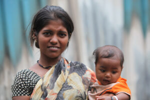A portrait of a poor Indian lady in her late teens with her baby boy.